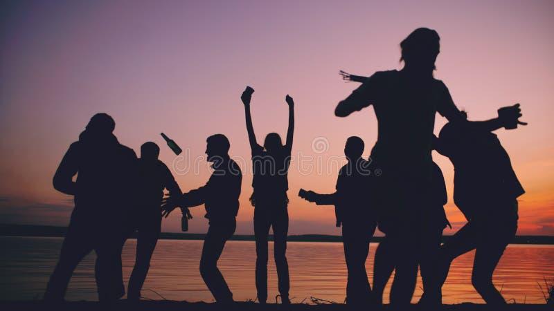 Силуэт людей танцев группы молодых имеет партию на пляже на заходе солнца стоковое фото