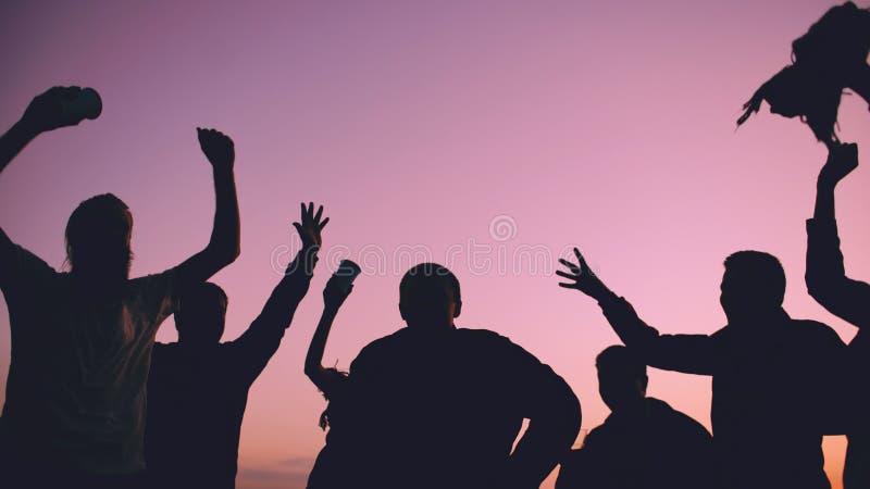 Силуэт людей танцев группы молодых имеет партию на пляже на заходе солнца стоковое изображение