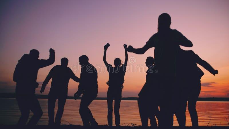 Силуэт людей танцев группы молодых имеет партию на пляже на заходе солнца стоковая фотография