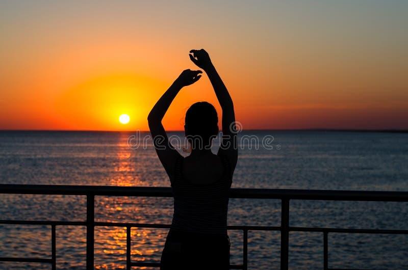 Силуэт маленькой девочки на заходе солнца Сумерки, волны Девушка стоковое фото rf