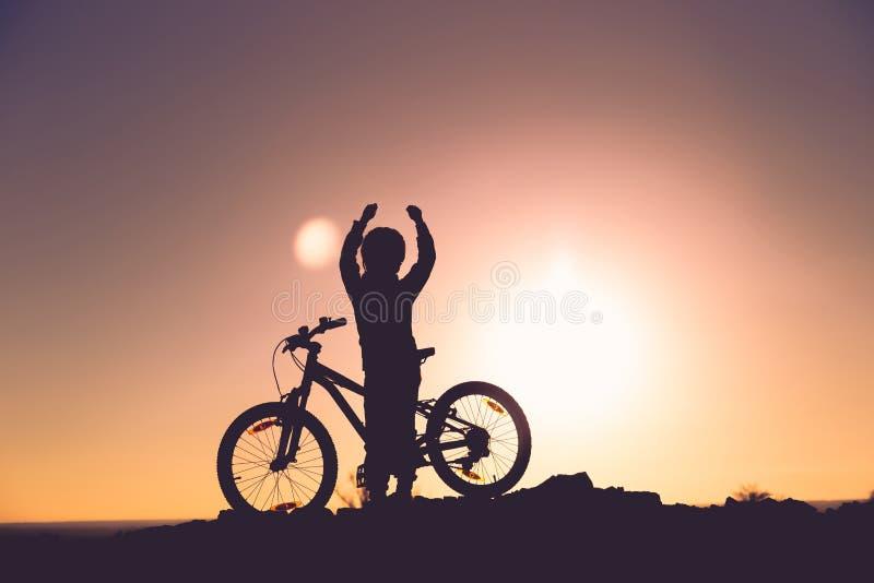 Силуэт маленькой девочки с велосипедом на заходе солнца стоковое изображение