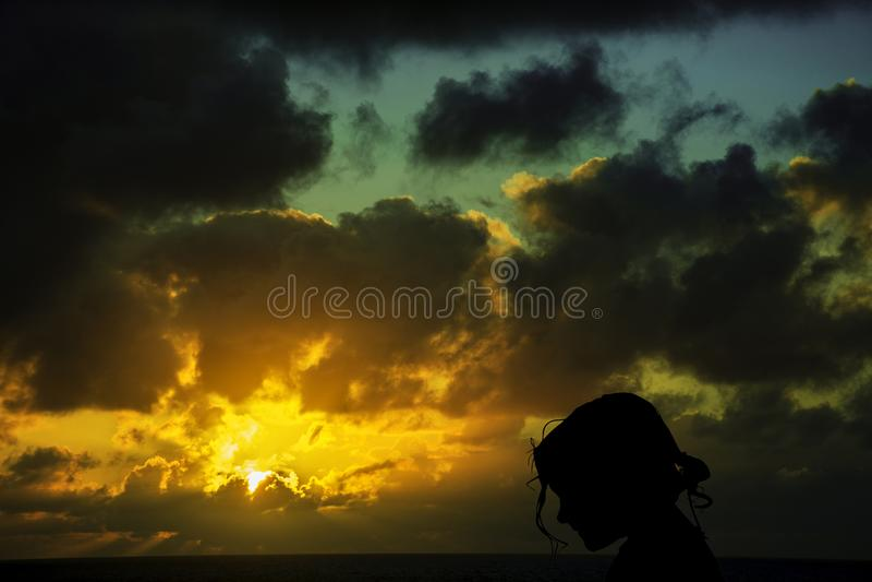 Силуэт маленькой девочки с восходом солнца над океаном в предпосылке стоковое фото rf