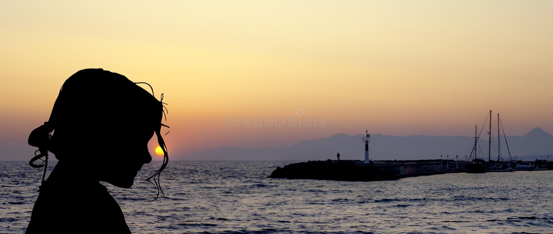 Силуэт маленькой девочки с заходом солнца сверх в Gouves, Крите стоковые фотографии rf