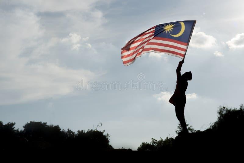 Силуэт мальчика держа малайзийский флаг празднуя День независимости Малайзии стоковое изображение rf