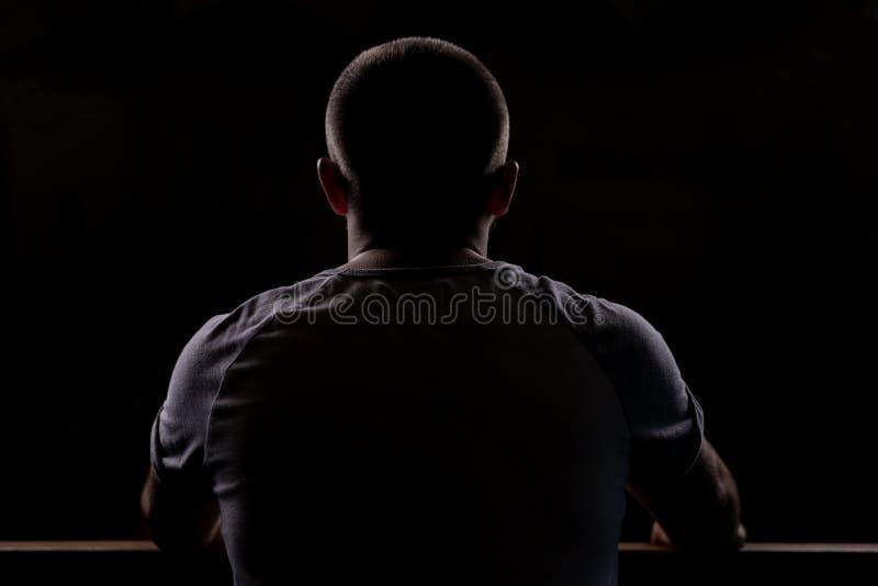 Силуэт молодого парня который сидит Взгляд конца-вверх от позади Backlight стоковые фото