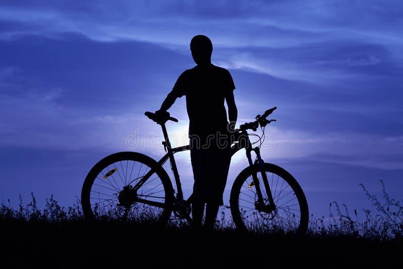 Силуэт молодого человека с велосипедом на заходе солнца стоковые изображения