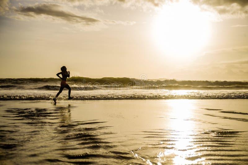 Силуэт молодой азиатской женщины бегуна спорта в идущей разминке стоковые изображения rf