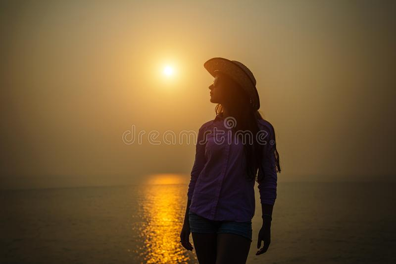 Силуэт молодой женщины в шляпе против захода солнца над морем Красивая худенькая девушка наслаждается миром и релаксацией на океа стоковое изображение rf