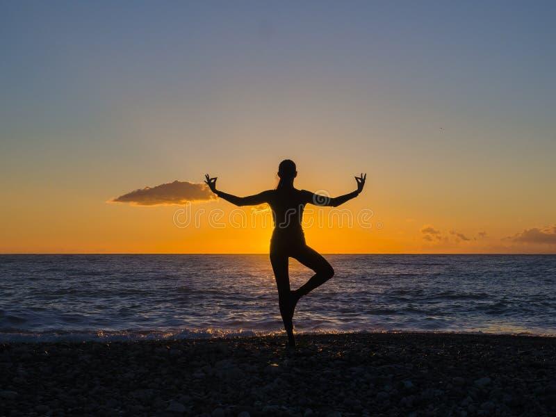 Силуэт молодой женщины делая тренировки на пляже моря во время захода солнца Йога, фитнес и здоровый образ жизни стоковая фотография