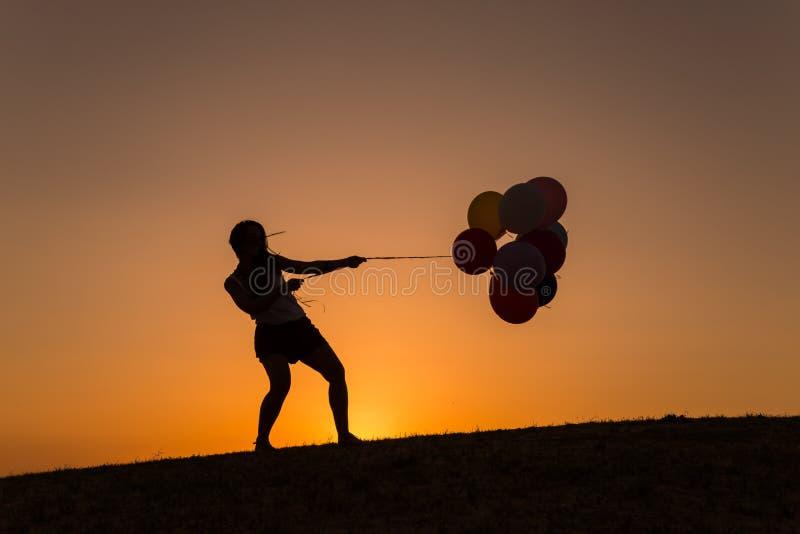 Силуэт молодой женщины играя с воздушными шарами на заходе солнца стоковое изображение rf