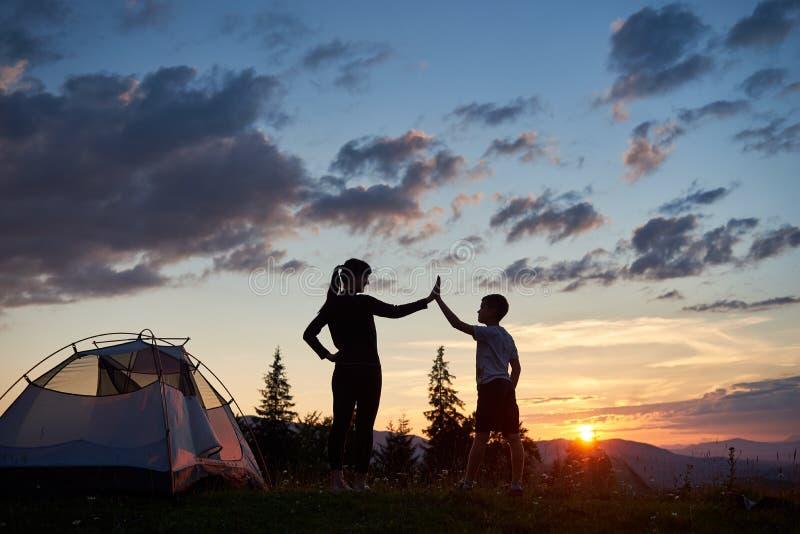 Силуэт молодой женщины и ребенка давая один другого высоко 5 около располагаться лагерем на зоре na górze горы стоковые изображения rf