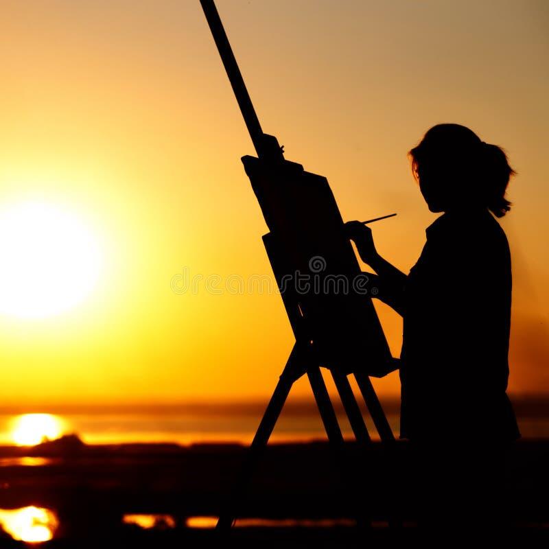 Силуэт молодой женщины крася изображение на мольберте на природе, диаграмме девушки с щеткой и палитре художника принимался за ис стоковые фотографии rf