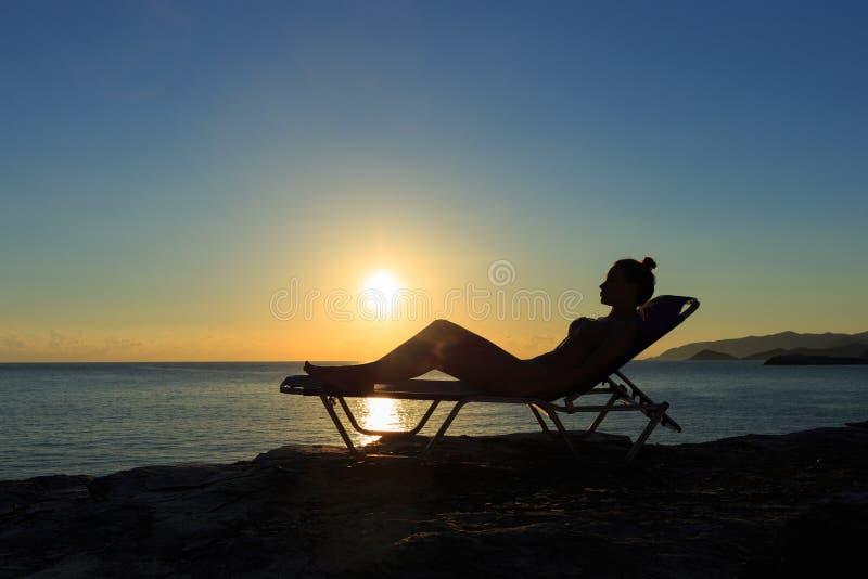 Силуэт молодой женщины лежит на deckchair на заходе солнца стоковые фотографии rf