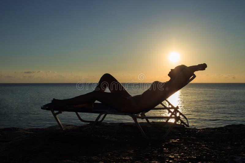 Силуэт молодой женщины лежит на deckchair на заходе солнца стоковое фото