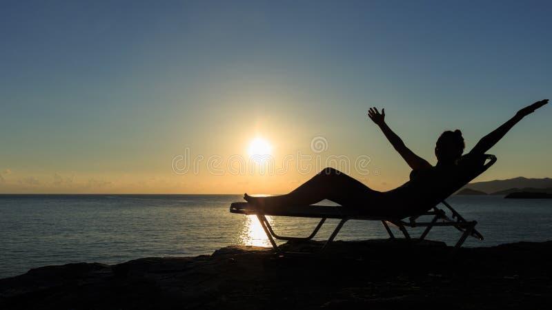 Силуэт молодой женщины лежит на deckchair на заходе солнца стоковые фото