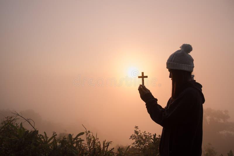 Силуэт молодой женщины моля с крестом на восходе солнца, христианской предпосылке концепции вероисповедания стоковая фотография rf
