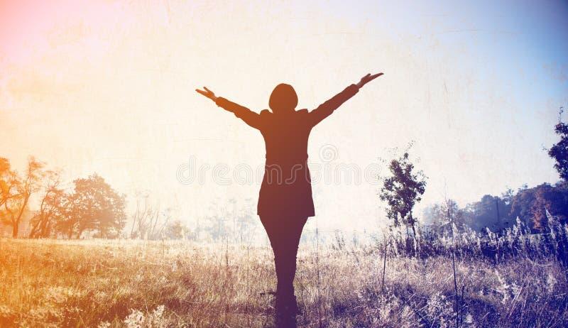Силуэт молодой женщины с открытыми руками стоковое фото