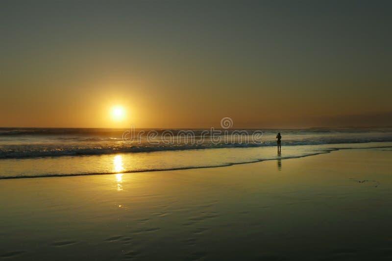 Силуэт молодой женщины фотографируя с мобильным телефоном изумительного красивого захода солнца на пляже стоковое изображение