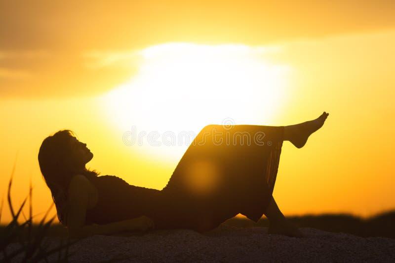 Силуэт молодой красивой девушки лежа в платье на песке и наслаждаясь заходом солнца, диаграммой женщины на пляже, стоковые фото