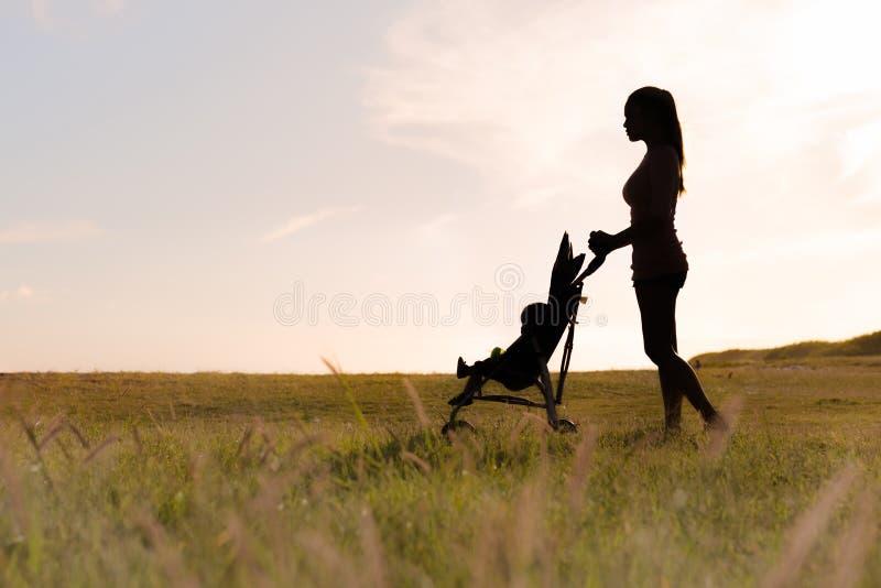 Силуэт молодой матери нажимая ее ребенка в прогулочной коляске через травянистое поле стоковое фото rf
