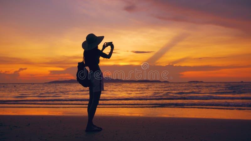 Силуэт молодой туристской женщины в шляпе принимая фото с мобильным телефоном во время захода солнца в пляже океана стоковое изображение rf