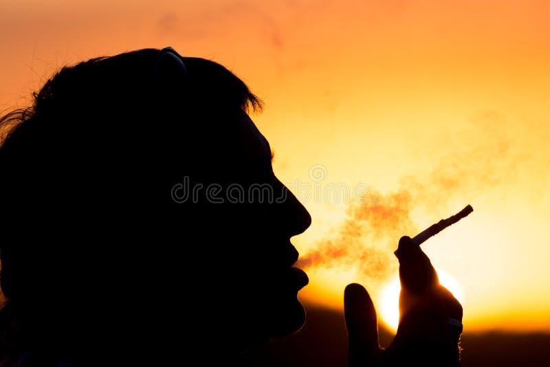 Силуэт мужских курильщиков в заходе солнца стоковые фотографии rf