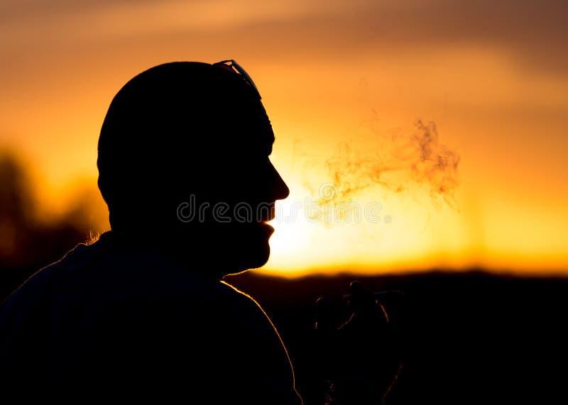Силуэт мужских курильщиков в заходе солнца стоковое фото rf