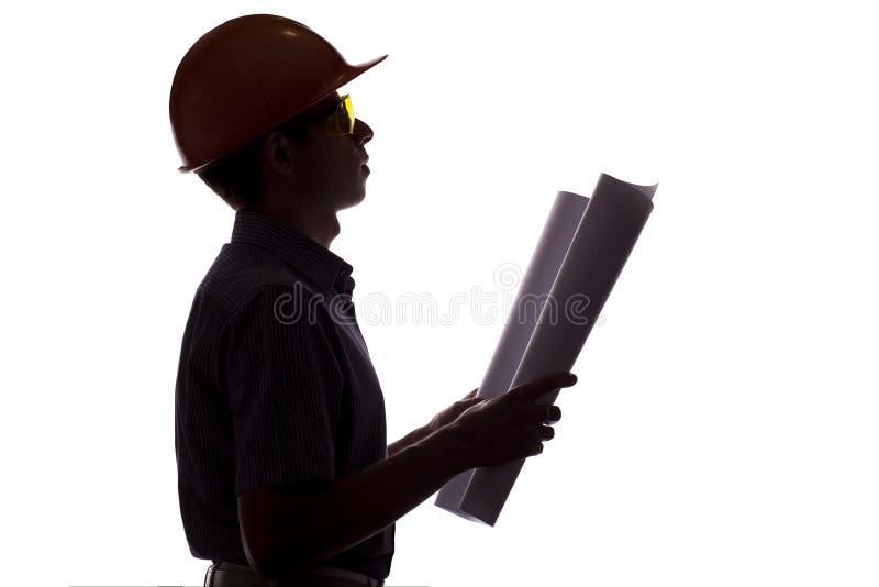 Силуэт мужского инженера по строительству и монтажу с проектом строительства, человек в официально одеждах и шлем контролируют ра стоковое изображение rf