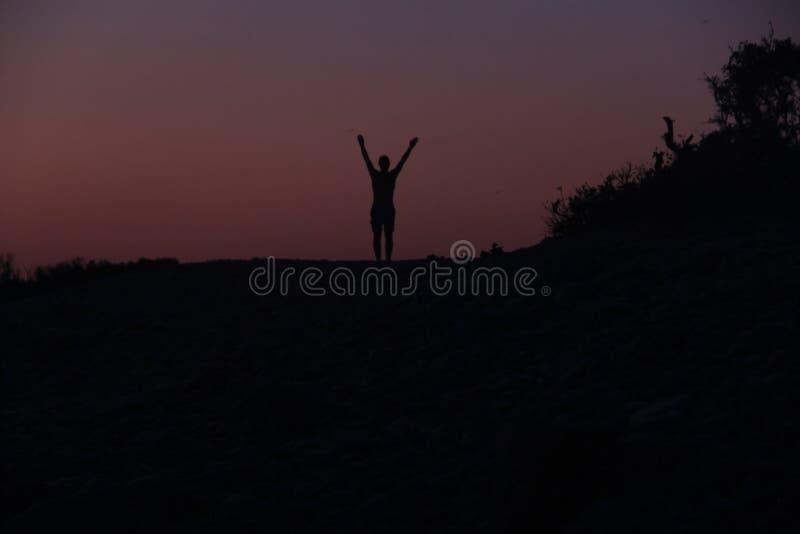 Силуэт мужчины на закате на пляже стоковая фотография