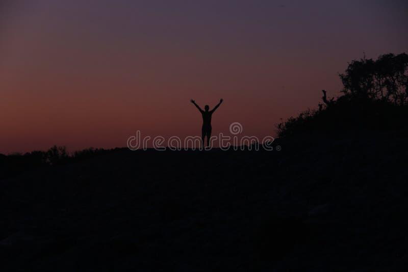 Силуэт мужчины на закате на пляже стоковые изображения rf