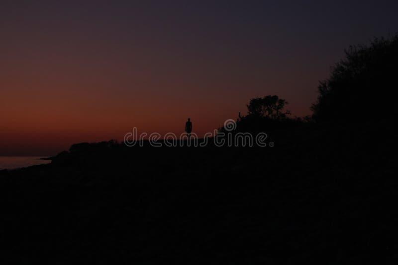 Силуэт мужчины на закате на пляже стоковое изображение