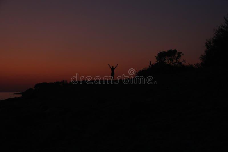 Силуэт мужчины на закате на пляже стоковые фото
