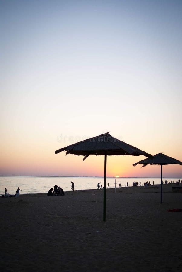 Силуэт на пляже с заходом солнца на море с зонтиком стоковые изображения rf