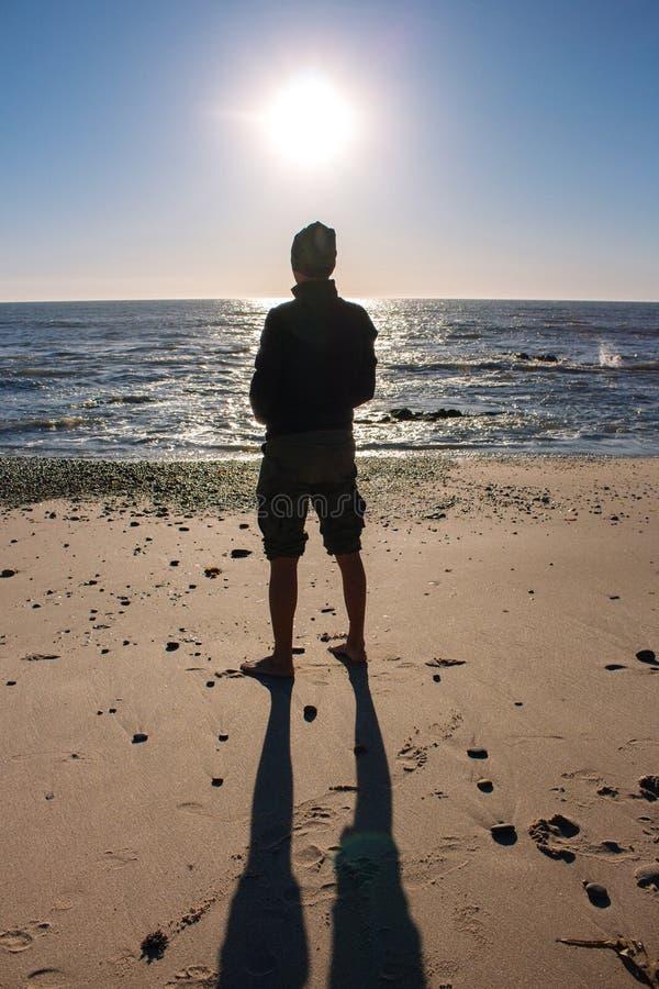 Силуэт неизвестного положения человека на пляже Концепция одиночества и уединения Силуэт людей на море и ясной предпосылке голубо стоковое фото