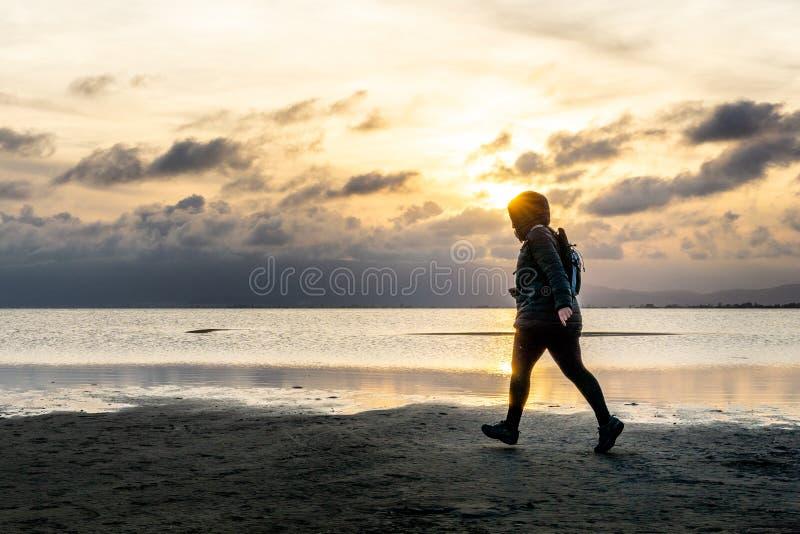 Силуэт непознаваемой женщины идя на пляж на заходе солнца стоковая фотография rf