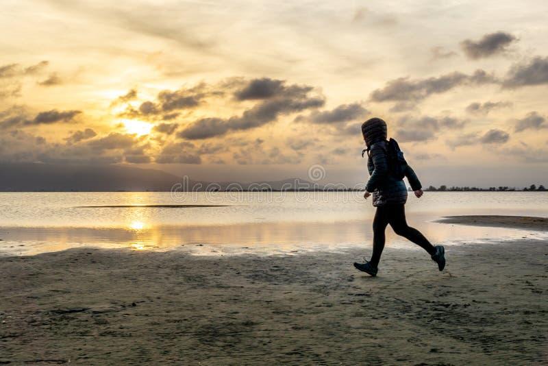 Силуэт непознаваемой женщины идя на пляж на заходе солнца стоковые изображения rf