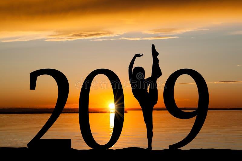 Силуэт 2019 Новых Годов танцев девушки на золотом заходе солнца стоковое фото
