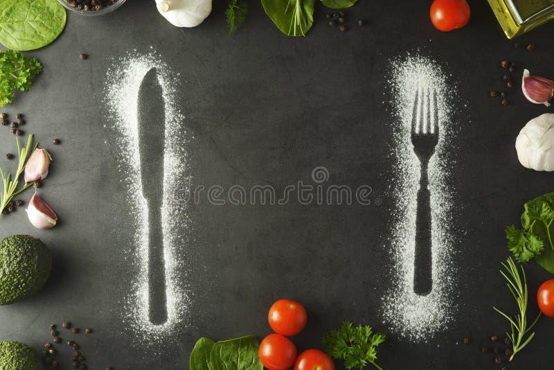 Силуэт ножа и вилки сделанный с мукой на темной предпосылке Концепция рамки еды r стоковая фотография rf