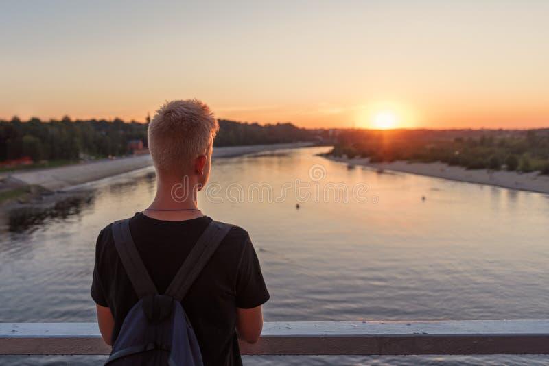 силуэт от задней части парня с предпосылкой заходящего солнца над речной водой стоковые изображения rf