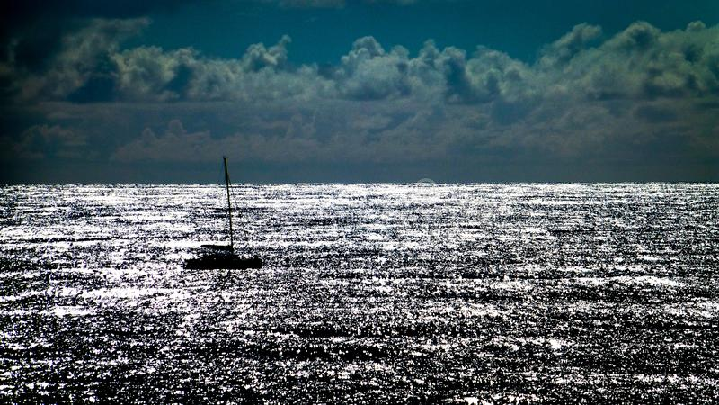 Силуэт парусника на заходе солнца с отражая морем стоковые изображения rf