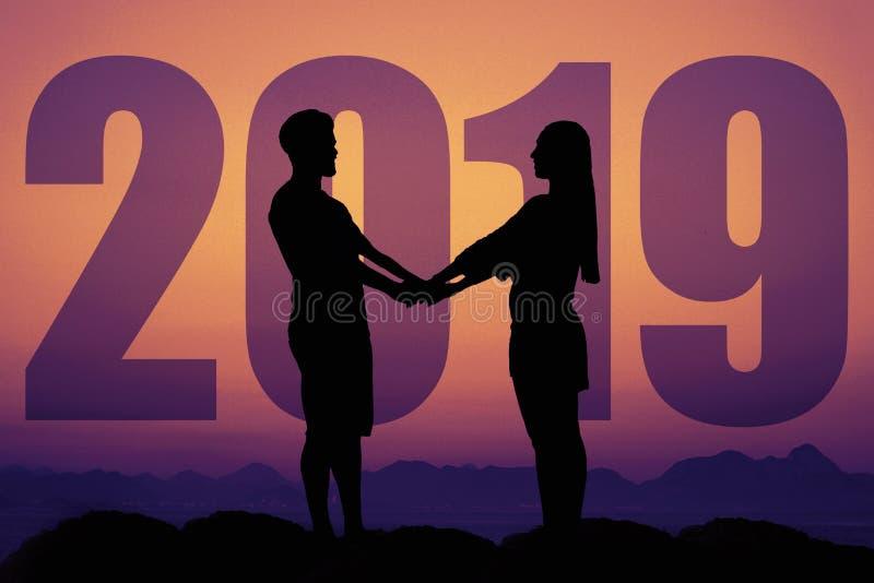 Силуэт пары влюбленности на заходе солнца с Новым Годом 2019 стоковое фото rf