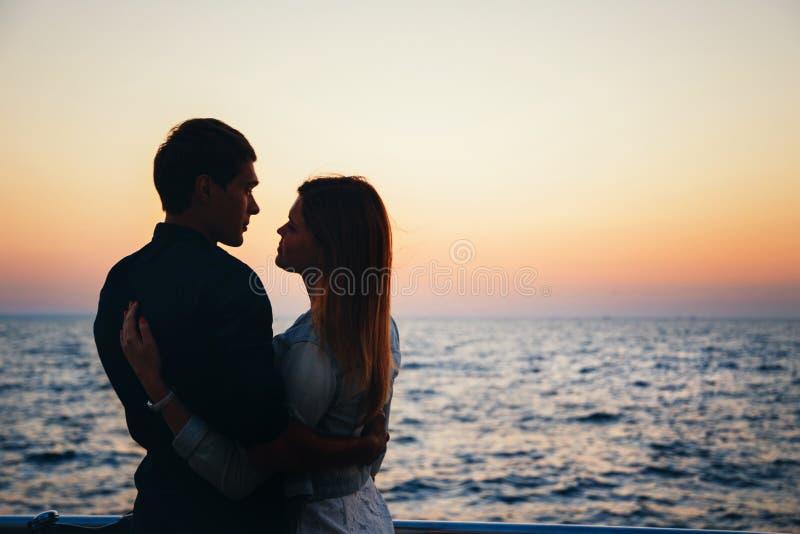 Силуэт пары на пляже на временени неба восхода солнца, пляже лета seashore на желтом голубом море горизонта вечера, заходе солнца стоковая фотография