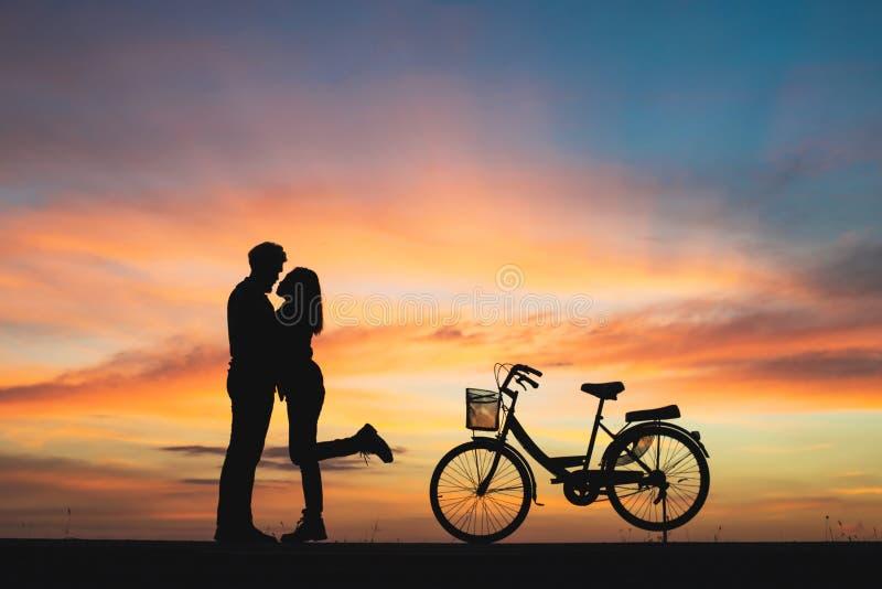 Силуэт пар в влюбленности целуя в заходе солнца Пары в влюбленности c стоковые изображения rf