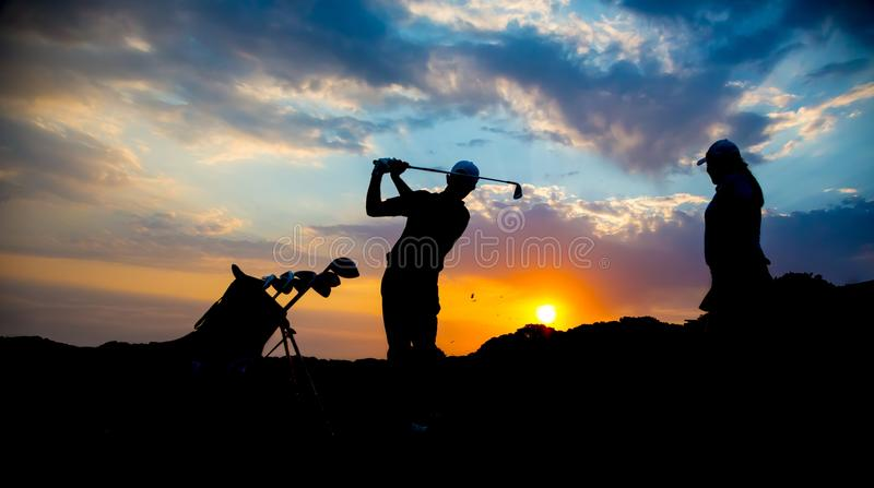 Силуэт пар игрока в гольф на заходе солнца стоковые фото