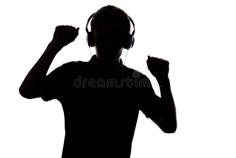 Силуэт подростка слушая к музыке в наушниках и danc стоковая фотография rf