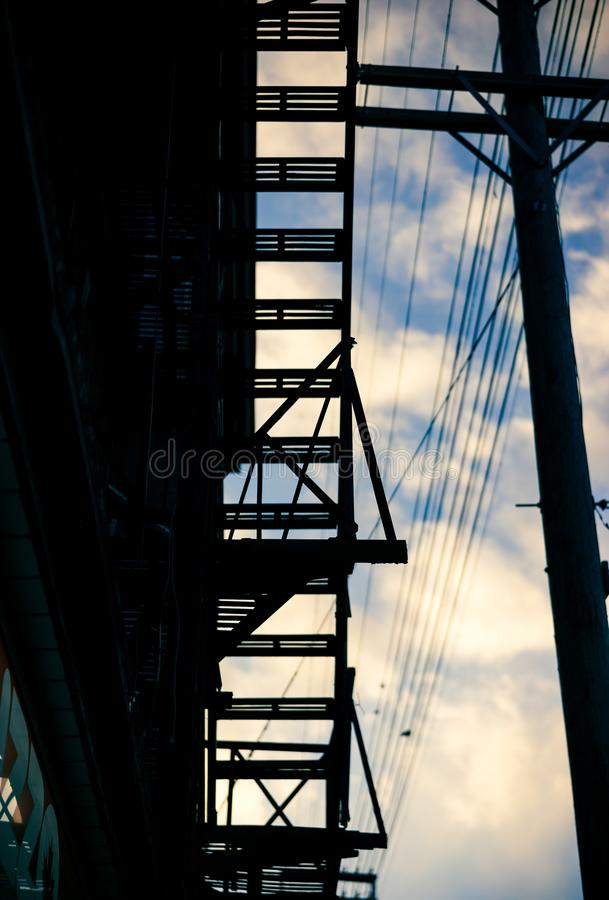 Силуэт пожарной лестницы жилого дома стоковая фотография