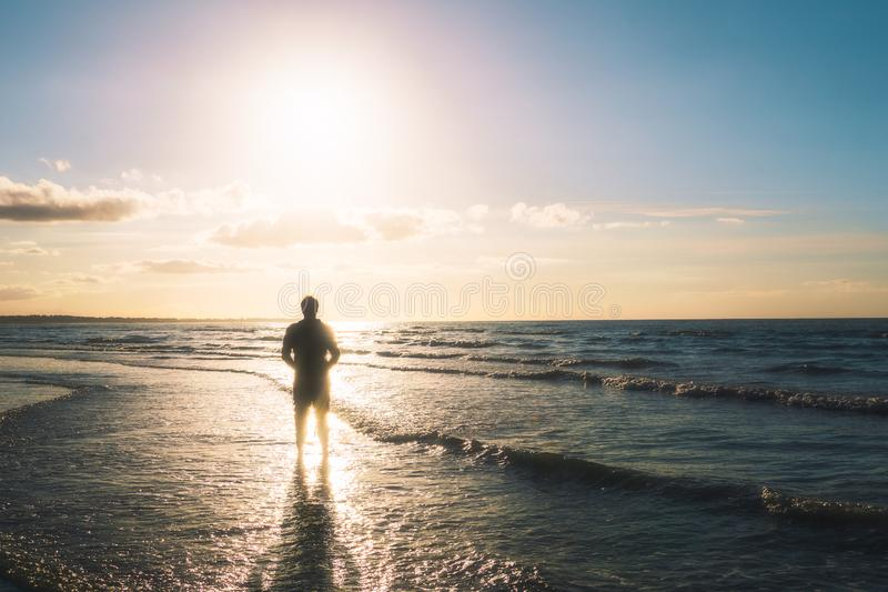 Силуэт положения молодого человека на seashore смотря на солнце Outdoors, лето, концепция свободы стоковые фото