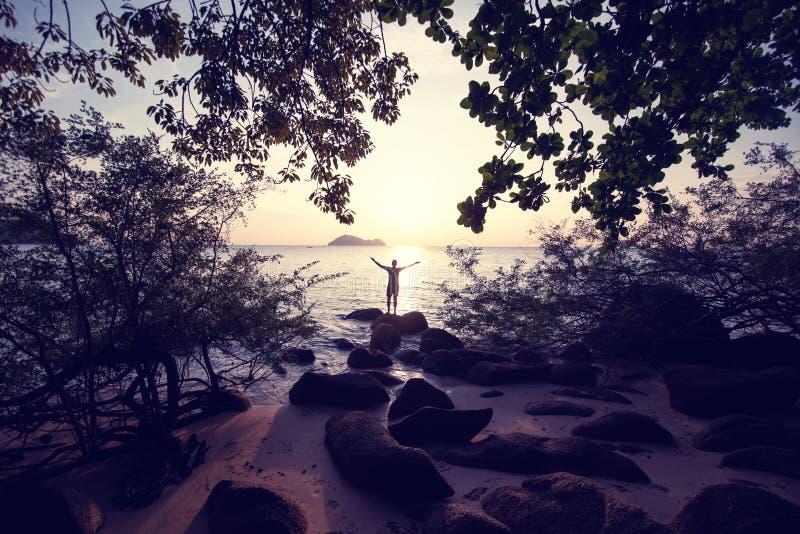Силуэт положения человека на камне морем на концепции захода солнца, человека и природы, перемещении каникул свободы образа жизни стоковое изображение