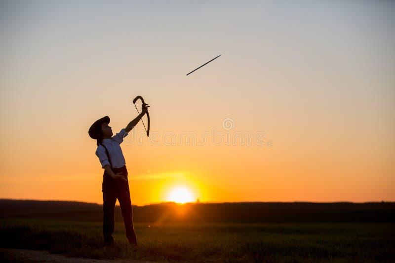 Силуэт ребенка играя с луком и стрелы, всходами archery стоковое изображение rf