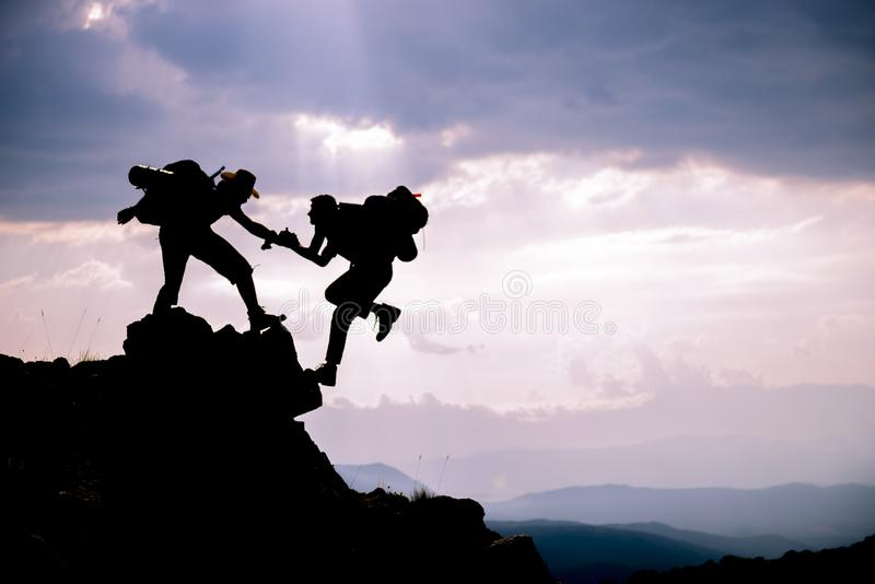 Силуэт руки помощи между альпинистом 2 Авантюрные люди; Hikers взбираясь на горе Помощь, риск, поддержка, помощь стоковое фото rf